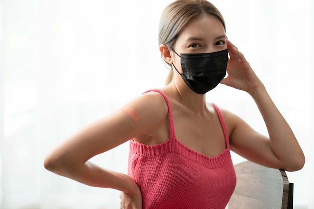 백신을받은 후 그녀의 팔을 보여주는 붕대로 마스크와 팔을 착용하는 여자