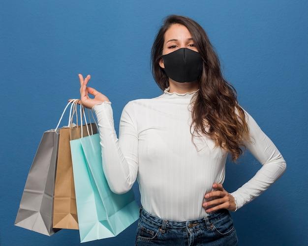 Женщина в маске и держащая хозяйственные сумки