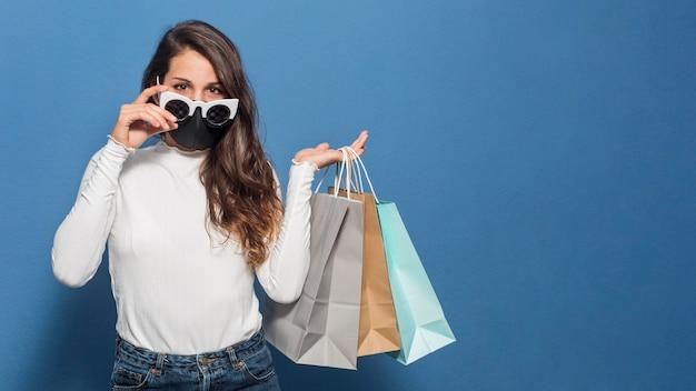 マスクを着用し、買い物袋を保持している女性