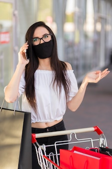 Woman wearing mask black friday shopping concept