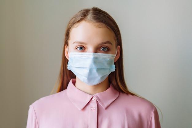 病気からの保護のためにマスクを身に着けている女性。家にいるように訴える。コロナウイルスの概念。