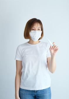 マスクを身に着けている女性がコロナウイルス、covid19、くしゃみ、咳、発熱、体の痛み、呼吸、痛みなどのインフルエンザの症状で病気になります。