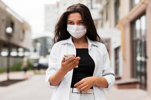 Женщина в маске по дороге на работу, глядя на смартфон