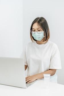 Una donna che indossa una maschera giocando un computer portatile e avendo una bottiglia di gel lavamani.