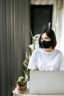 A woman wearing a mask and playing a laptop.