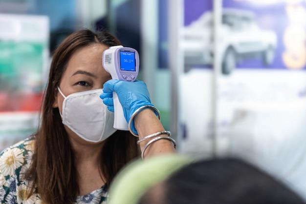 サーモスキャンまたは温度計の銃でマスクを着た女性がコロナウイルスをスクリーニング