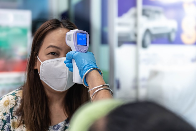 Woman wearing mask with thermoscan or thermometer guns screening for coronavirus