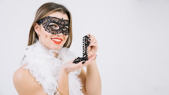 Woman wearing masquerade carnival mask holding necklace over white background