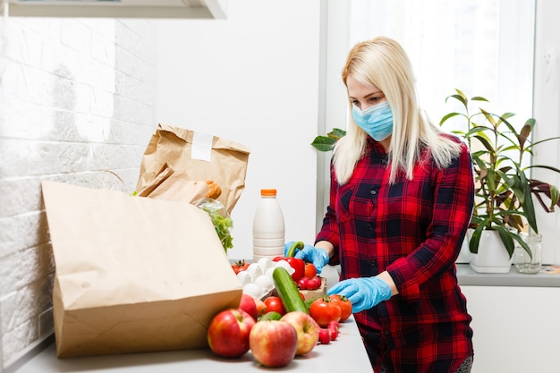 Woman wearing medical face mask disassembles food bags at home in the kitchen. quarantine. health concept. corona virus. order of products online. delivering products to home
