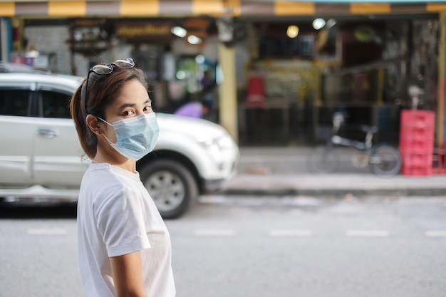 거리 보도와 야시장을 걷는 동안 의료용 안면 마스크를 쓴 여성은 코로나바이러스나 코로나 바이러스 질병(covid-19)을 예방합니다. 건강, 생활 개념