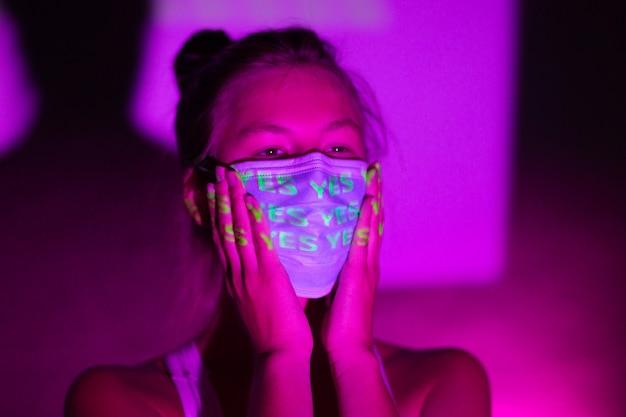 Женщина в медицинской маске в темноте.