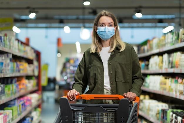 Женщина, носящая медицинскую маску, толкает корзину в супермаркете. молодая девушка выбирает, ищет продукты для покупки. девушка ходит по супермаркету или магазину. радостная красивая женщина, идущая в торговом центре