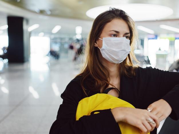 手荷物のクローズアップを待っている医療マスク空港を身に着けている女性