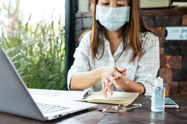 コロナウイルスの危機の間、医療用マスクを着用して手を洗う女性。 Premium写真
