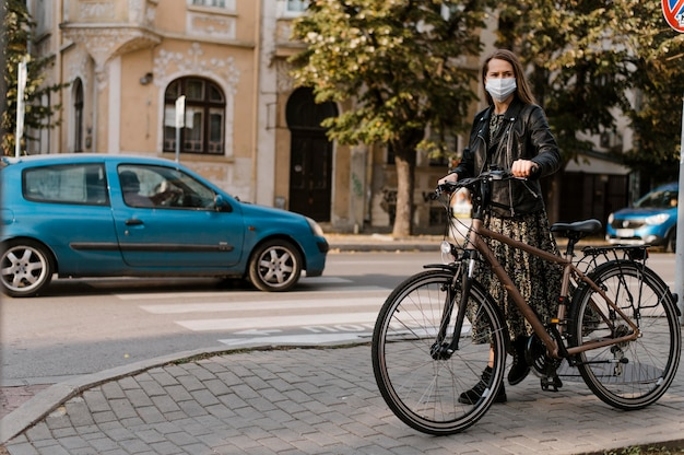 Woman wearing medical mask and bicycle long view