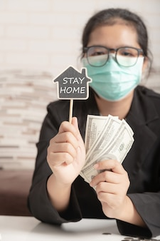 A woman wearing a medical mask and a black suit showing the symbol stay home