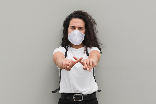 Woman wearing medical mask and forming an x with her fingers