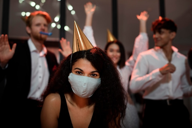 Woman wearing a medical mask next to her friends on new year's eve party