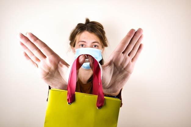 Женщина в медицинской маске держит сумку для покупок