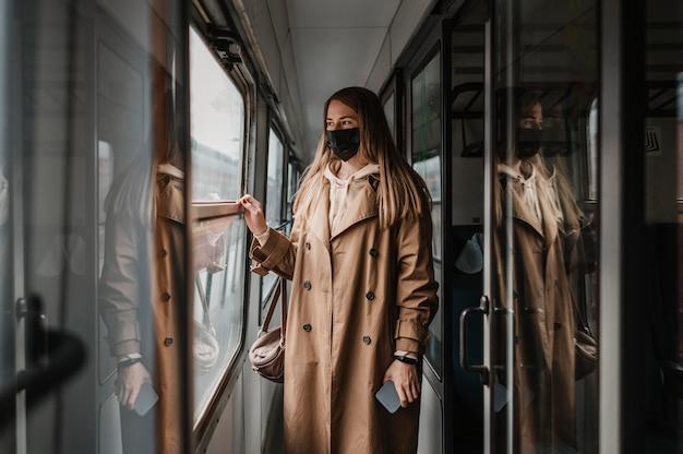 기차에서 의료 마스크를 착용하는 여자