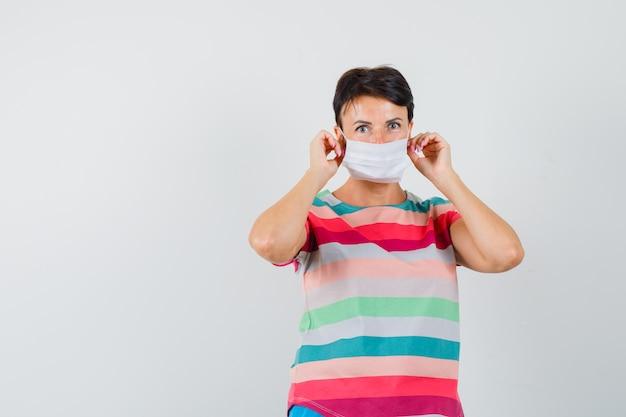 스트라이프 티셔츠에 의료 마스크를 착용하고 조심스럽게 보는 여자.