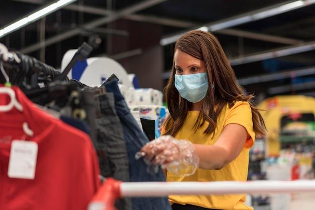 Женщина в медицинской маске, глядя на джинсы