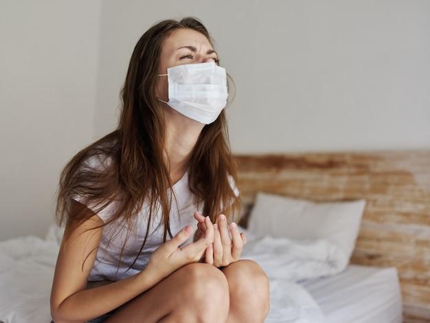 屋内ベッドコロナウイルス隔離に医療マスクを身に着けている女性