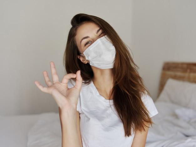 医療マスクを身に着けている女性ポジティブハンドジェスチャー寝室 Premium写真