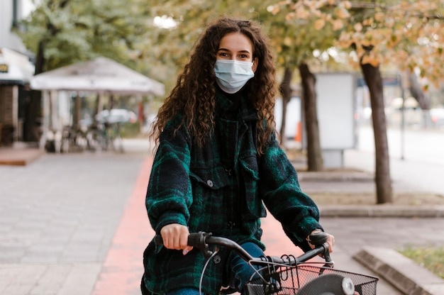 Woman wearing medical mask and riding the bicycle front view