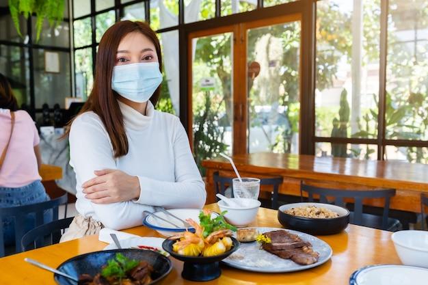 식당에서 코로나 바이러스를 보호하기 위해 의료 마스크를 착용하는 여성