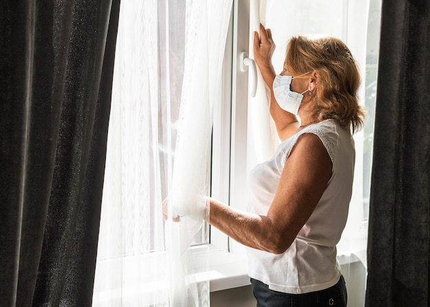 Woman wearing a medical mask while watching out the window