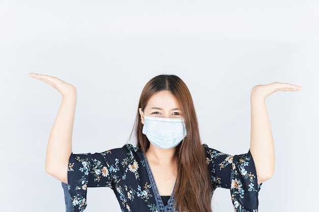 Woman wearing a medical protection face mask and her hands carry something on her head