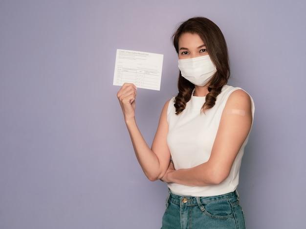 腕に絆創膏が付いた医療用保護衛生マスクを着用し、コロナウイルスワクチン接種キャンペーンコンセプトのワクチンを接種した後、ワクチン接種済みの記録カードを提示している女性。