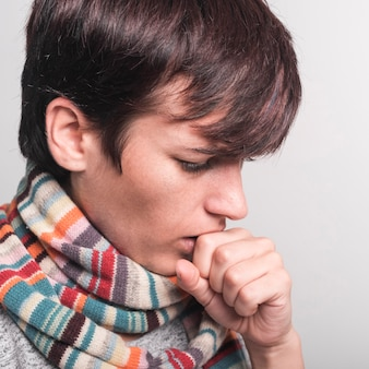 Woman wearing multicolored scarf around neck coughing against gray backdrop