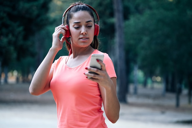 Woman wearing music helmets and using her mobile in a park