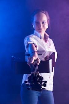 어쿠스틱 기타를 보여주는 사무실 셔츠를 입고 여자