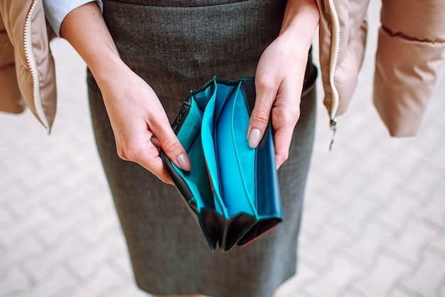 Woman wearing office suit holding open empty wallet