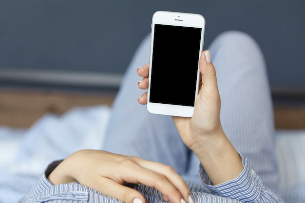 Woman wearing pajamas and holding smartphone