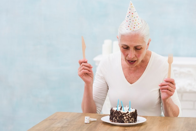 Woman wearing party hat holding wooden knife and fork looking at birthday cake on table