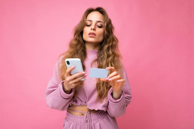 모바일을 사용하여 분홍색 배경 위에 절연 분홍색 옷을 입고 여자