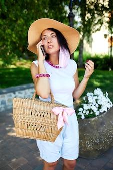 Женщина в розовой маске для лица и разговаривает с кем-то по мобильному телефону в парке на открытом воздухе, молодая женщина с мобильным телефоном, пандемия, вспышка коронавируса, две волны