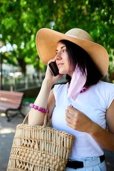 ピンクのフェイスマスクを着用し、屋外の携帯電話ウォーキングパークで誰かと話している女性、携帯電話を持った若い女性、パンデミック、コロナウイルスの発生、