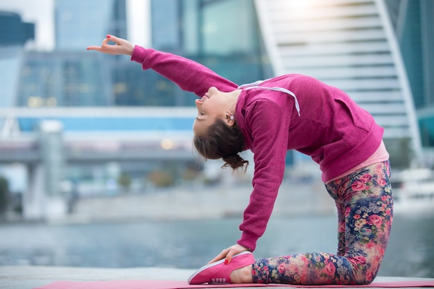 Woman wearing pink sportswear in camel pose against city background
