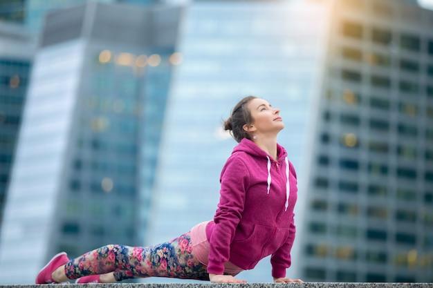 上向きの犬の運動にピンクのスポーツウェアを着ている女性