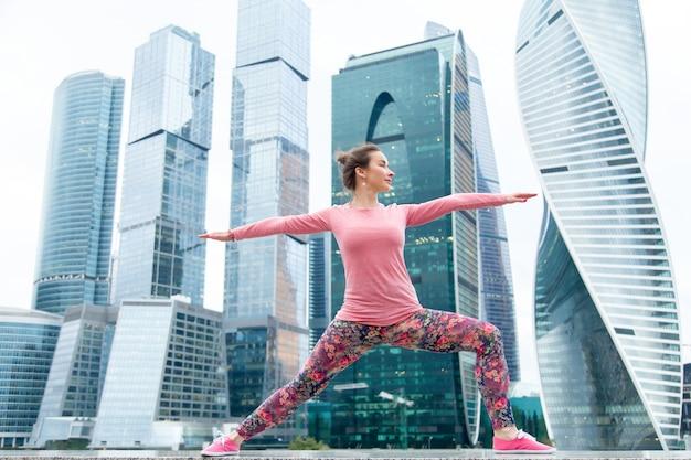 Woman wearing pink sportswear in warrior two pose