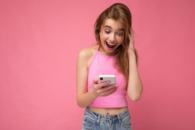 빈 공간이 손에 들고와 gadjet에서 온라인으로 통신하는 휴대 전화를 사용하여 분홍색 배경에 고립 분홍색 최고 poising 입고 여자.