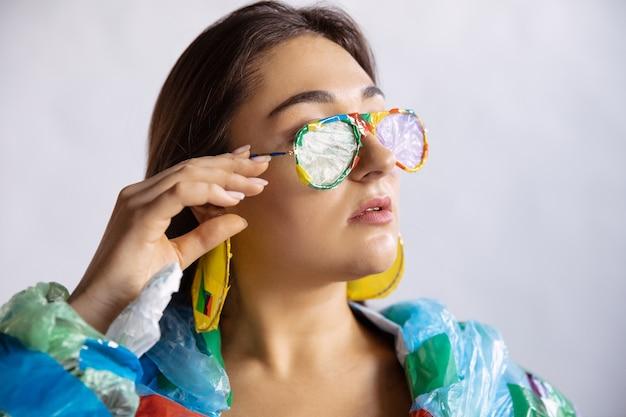 Женщина в пластике на белой стене. женская модель в одежде и обуви из мусора. мода, стиль, переработка, эко и экологическая концепция. слишком много загрязнения, мы едим и забираем его.