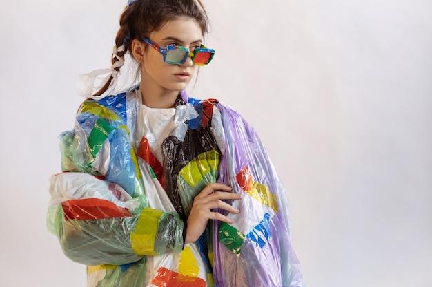 白い壁にプラスチックを身に着けている女性。ゴミで作られた服や靴の女性モデル。ファッション、スタイル、リサイクル、エコ、環境のコンセプト。汚染が多すぎるので、私たちはそれを食べて飲んでいます。