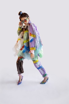 Woman wearing plastic on white wall. female model in clothes and shoes made of garbage. fashion, style, recycling, eco and environmental concept. too much pollution, we're eating and taking it.