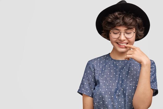 Woman wearing polka dot blouse and big hat